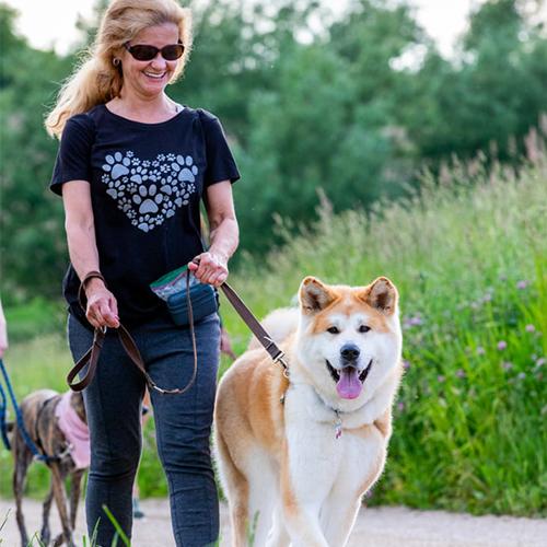 woman walking dog in prairie