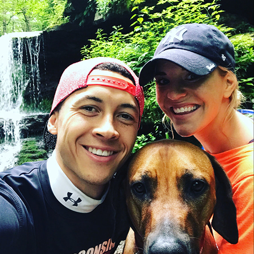 couple with dog. waterfall behind