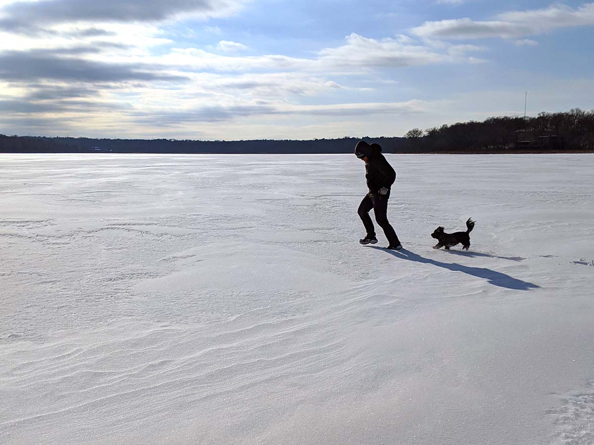 man and little dog running on frozen lake covered in snow