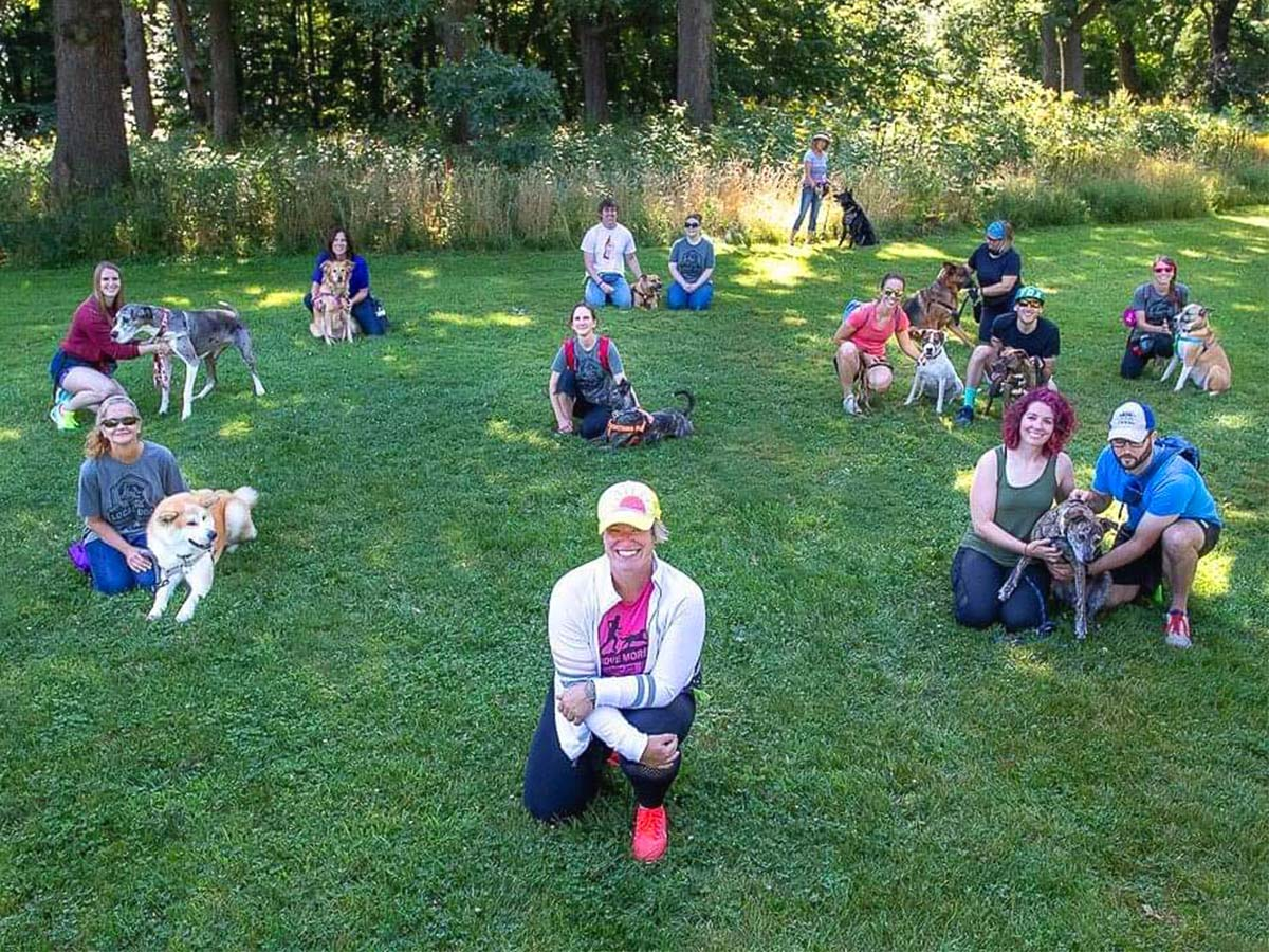 group of people sitting on grass with dogs